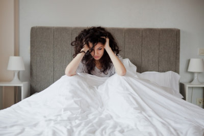 Woman having a depression in her bed looking sad