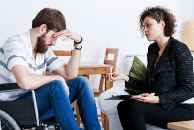 Home assistant talking with depressed invalid patient in wheelchair